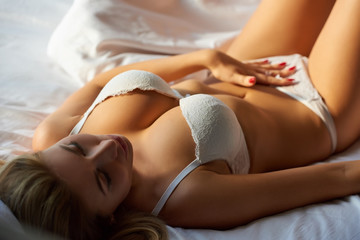 Beautiful girl in bed. Caucasian girl with big breasts.