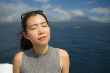 young beautiful and sweet Asian Chinese woman smiling happy enjoying sea breeze at tropical ocean landscape