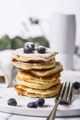 Pile of american pancakes with blueberries and powdered sugar.