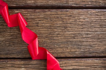Red ribbon on wooden table