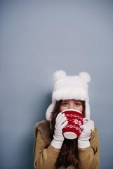Girl drinking hot chocolate at studio shot .