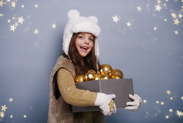 Cheerful girl holding box of christmas balls