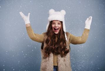 Cheerful girl among snow falling