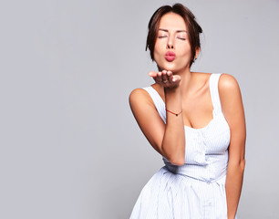 Portrait beautiful cute brunette woman model in casual summer dress with no makeup isolated on gray. Giving a kiss