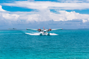 Maldivian airlines seaplane landing in blue sea