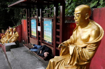 A man takes a nap between life-size gilded Arhan statues at Ten Thousand Buddhas Monastery in Hong Kong