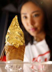 Business owner Faye makes final touches to a gold leaf soft ice cream at her Small Potatoes Ice Creamery shop in Singapore