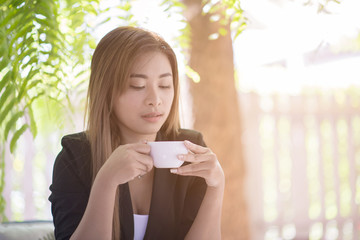 Young businesswoman sitting and drinking coffee happily outside the office at lunch break. Relaxation, Coffee Break