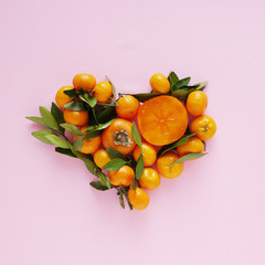 Heart made from fruits. Composition of small tangerines with leaves and persimmons on a pink background. Pattern of fruits, top view, flat lay.