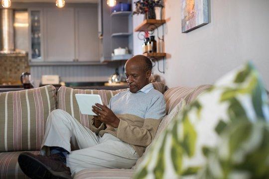 Senior man using tablet computer in living room