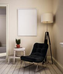 Sessel mit schwarzem Polster und Pflanze sowie Bilderrahmen vor beigefarbener Wand