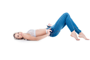 sexy girl lying and taking off jeans, isolated on white