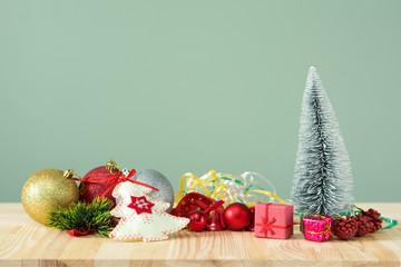 Christmas background. Little Christmas tree with decorations on a light wooden table. Green background. Space for text. New Year's background.