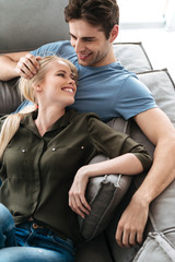 Happy lovers lying on sofa and hugging in living room