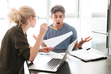 Young busy man has a quarrel with his woman while working at home