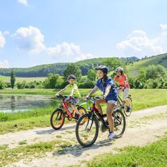 Mutter mit Kindern beim Radfahren am See