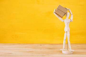 wooden dummy figure holding present box over yellow background.