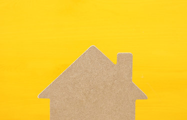 Imahe of wooden house model over yellow background. Real estate concept.