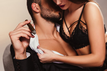handsome businessman with cigar kissing beautiful girl in lingerie