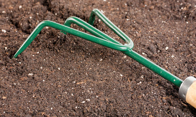 Small gardening fork in black composted soil