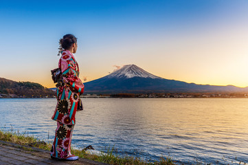 Wall Mural - Asian woman wearing japanese traditional kimono at Fuji mountain. Sunset at Kawaguchiko lake in Japan.
