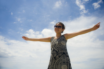 young happy and excited Asian Chinese woman posing alone isolated on a Summer blue sky looking cheerful and relaxed enjoying