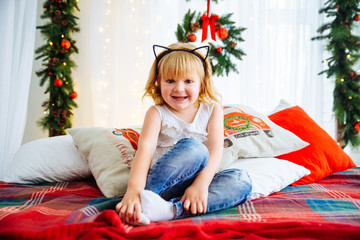 Cute toddler girl on the bed with christmas decoration