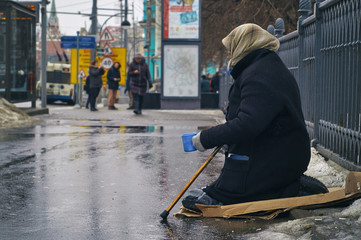 Old female beggar asking for money on Moscow street in winter