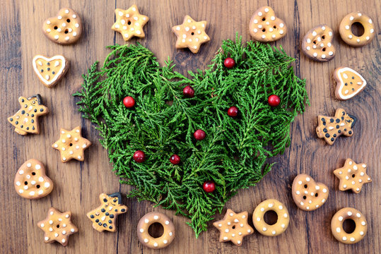 Christmas bakery background with cookies and heart of pine twigs with red fruits
