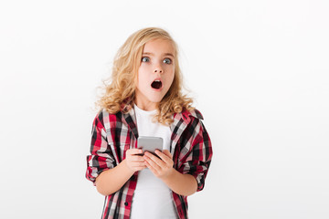 Portrait of a shocked little girl holding mobile phone
