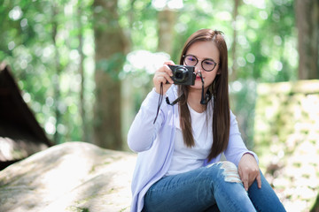 Beautiful girl holding a camera in a garden with a big tree.