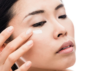 Close-up of young Asian woman applying anti-wrinkles eye moisturizer against white background