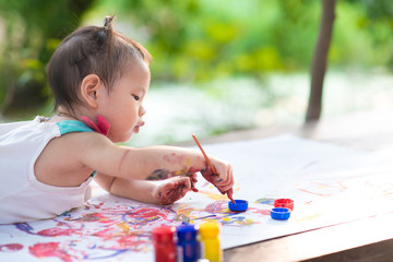 Cute little Asia child painting with paintbrush outdoor