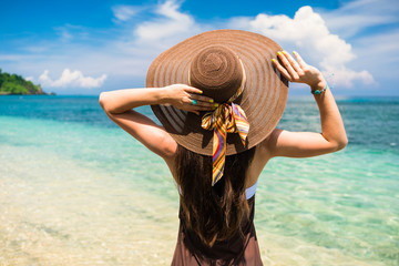 Woman in summer vacation wearing straw hat and beach dress enjoying the view at the ocean