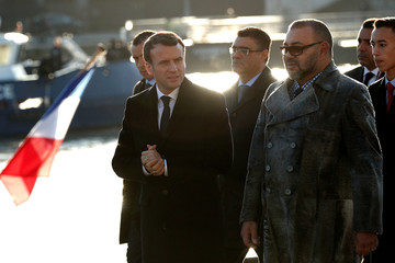 French President Emmanuel Macron and Morocco's King Mohammed VI board the 'Mirage' boat on the Seine river prior going to the Ile Seguin near Paris as part of the One Planet Summit