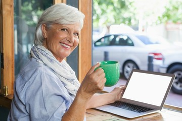 Portrait of smiling senior woman holding coffee cup while