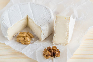 camembert and walnut on wooden background