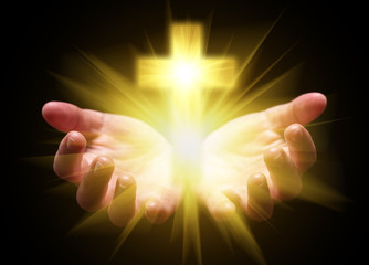 Hands cupped and holding or showing Cross or Crucifix with bright, glowing, shining light. Concept for Christian, Christianity, Catholic religion, divine, heavenly, celestial or god. Black background