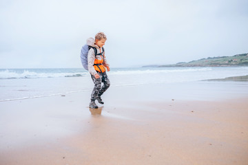 Boy little backpacker runs from ocean waves on the deserted beach in rainy day