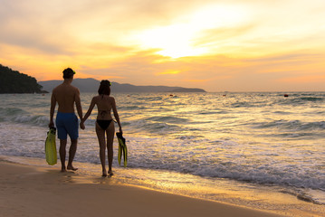 Summer Vacation.  Couple walking holding hands on tropical on the beach sunset time in holiday after snorkel swim. Honeymoon holidays people relaxing together on summer travel destination.  Valentine
