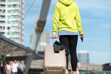 Back view of female tourist with suitcase in hand of hold passport while walking up staircase in city building, Travel concept