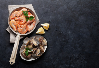 Fresh seafood on stone table. Scallops and shrimps