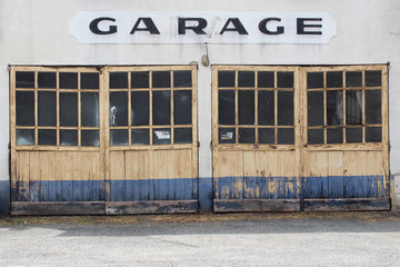 Old wooden and glass doors, painted in retro yellow and blue colours with hand painted garage sign above