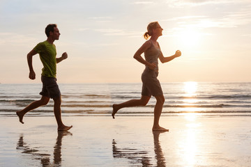 Happy young couple jogging on beautiful sunset sea beach. Sporty lifestyle concept.