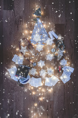 Top view of a Christmas tree composition with medical equipment: stethoscope, blood pressure measurement device, syringes, pills, Christmas lights and snowflakes decoration on wooden background