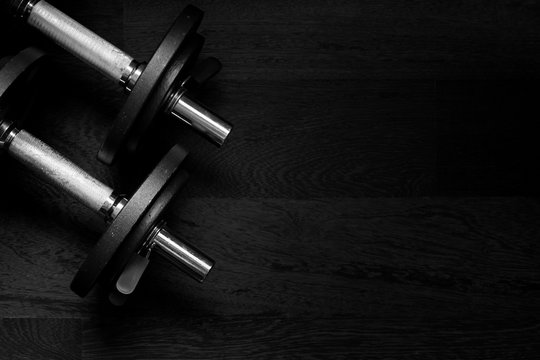 Black metal weights on wooden background, high contrast dark toned image