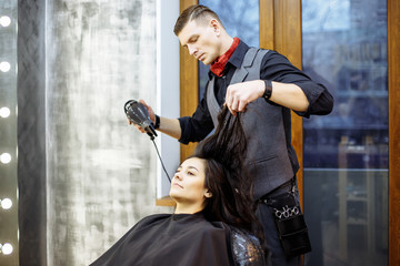 Hairdresser dries hair with a hairdryer in beauty salon.
