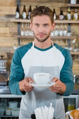 Portrait of smiling waiter serving cup of coffee at counter