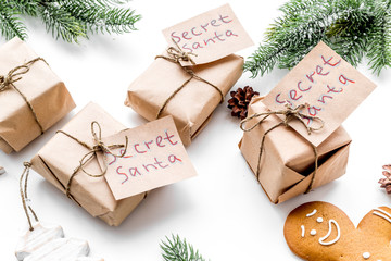 Christmas traditions. Gift boxes with notes Santa Secret near spruce branch and gingerbread cookies on white background close up