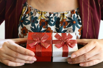 Close up red  and white gift boxs in woman 's hand